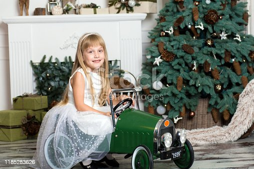 486524205 istock photo little girl in a white dress rides a vintage children's car in Christmas decorations against the background of a Christmas tree and a fireplace. Happy New year and merry Christmas 1185283626