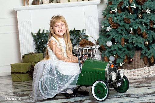 486524205 istock photo little girl in a white dress rides a vintage children's car in Christmas decorations against the background of a Christmas tree and a fireplace. Happy New year and merry Christmas. 1185283709