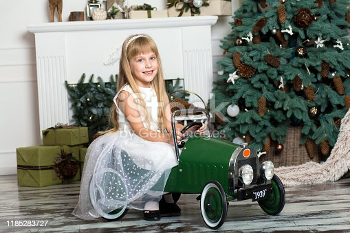 486524205 istock photo little girl in a white dress rides a vintage children's car in Christmas decorations against the background of a Christmas tree and a fireplace. Happy New year and merry Christmas. 1185283727