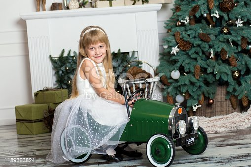 486524205 istock photo little girl in a white dress rides a vintage children's car in Christmas decorations against the background of a Christmas tree and a fireplace. Happy New year and merry Christmas 1189363824