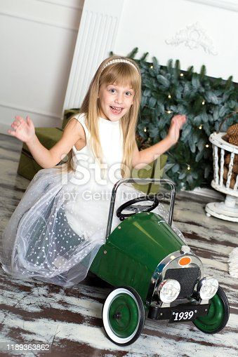 486524205 istock photo little girl in a white dress rides a vintage children's car in Christmas decorations against the background of a Christmas tree and a fireplace. Happy New year and merry Christmas 1189363862