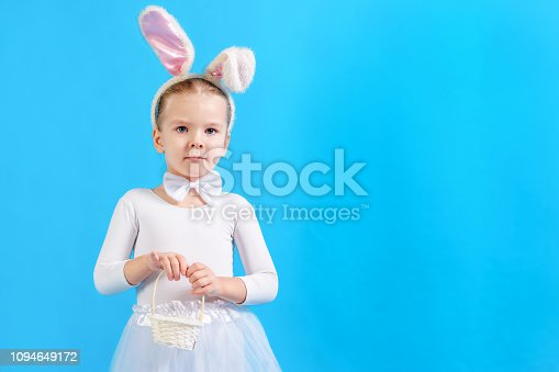 155096501 istock photo Little girl in a white Easter bunny costume. The child is holding a small basket. Copy space. Bright photo with place for text. 1094649172