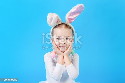 155096501 istock photo Little girl in a white Easter bunny suit on a bright blue background. Beautiful emotional child. Bright festive photo. 1094649080