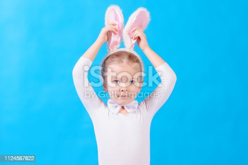 istock Little girl in a white rabbit costume on a blue background. A child touches his ears. Beautiful photo with space for text and advertising. 1124567622