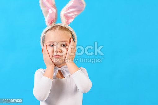 155096501 istock photo Little girl in a white rabbit costume on a blue background. The child holds his head. Beautiful emotional photo. 1124567630