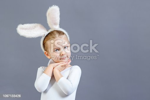 155096501 istock photo Little girl in a white rabbit costume on a gray background. Copy space. Advertising photo with space for text. 1097133426