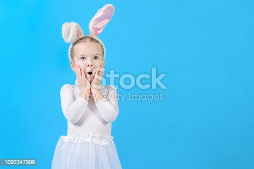 155096501 istock photo Little girl in a white rabbit costume. Surprised baby. Cute bunny, holiday symbol. Bright photo on a blue background, with copy space. 1092347998