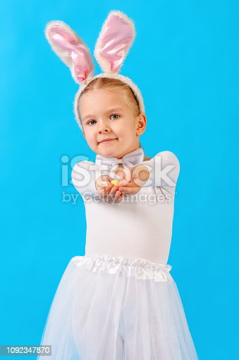 155096501 istock photo Little girl in a white rabbit costume. The child is holding an Easter egg. Cute bunny, holiday symbol. Bright photo on blue background. 1092347870