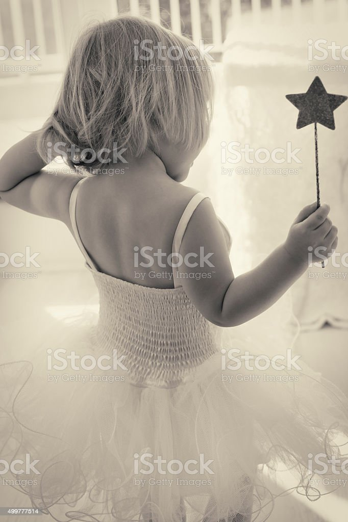Little girl in a white tutu and magic wand stock photo