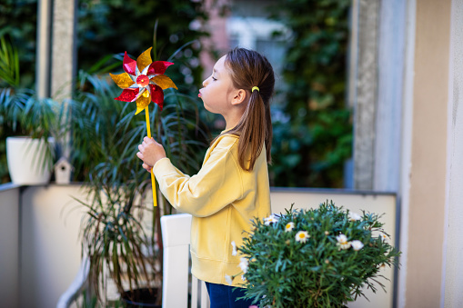 Little girl in a yellow sweatshirt on the balcony blowing on a windmill
