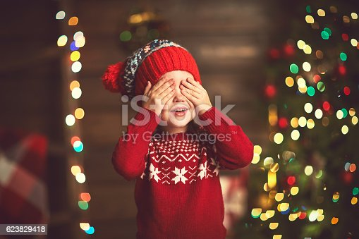istock little girl  in anticipation of a Christmas miracle and gift 623829418