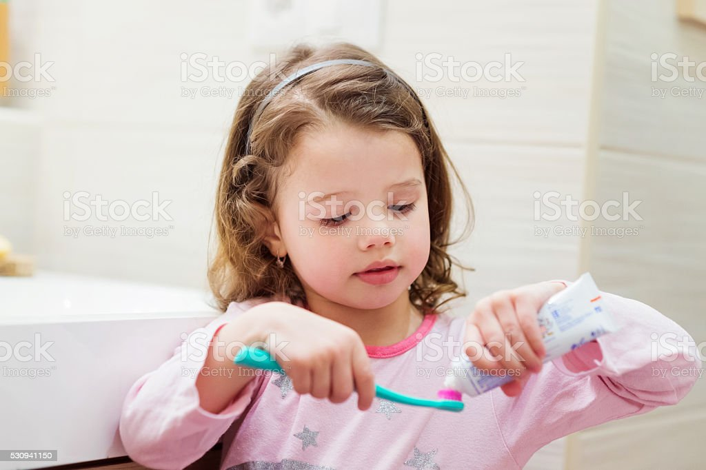 Little girl in bathroom putting a toothpaste on toothbrush stock photo