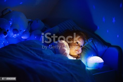 istock Little girl in bed with night lamp in dark nursery 611886898