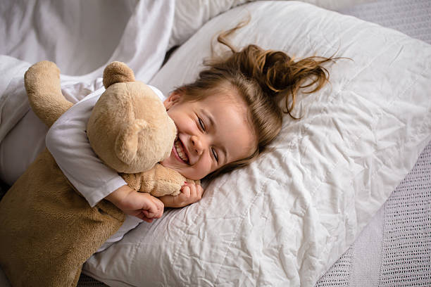little girl in bed with soft toy the emotions - foto de stock