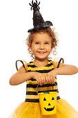 istock Little girl in bee costume with Halloween bucket 513254831
