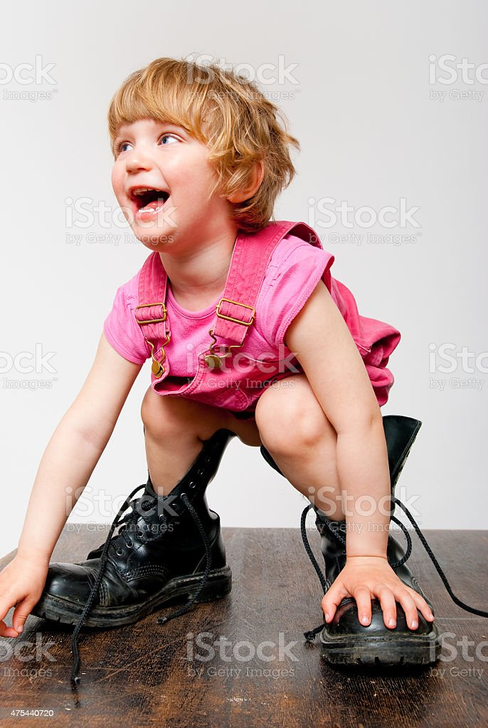little girl in big boots stock photo