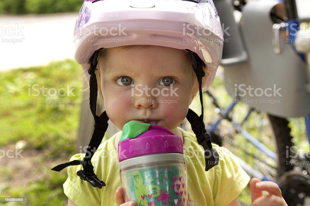 Little girl in bike helmet drinking water stock photo