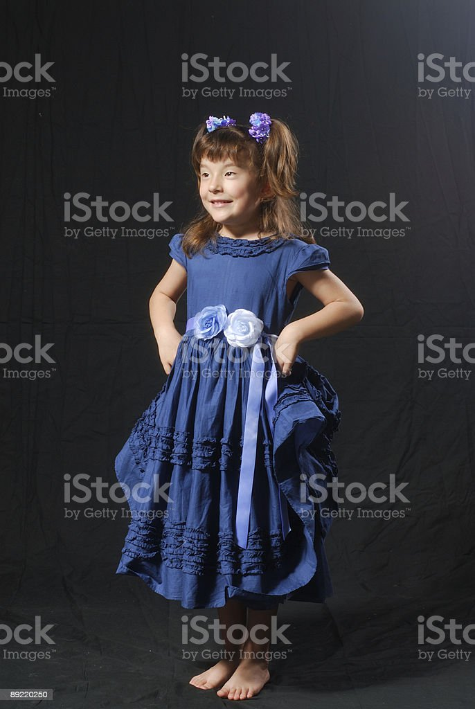 Little girl in blue dress standing hands on her hips royalty-free stock photo