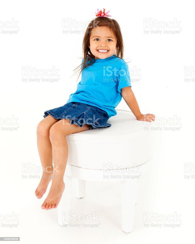 Little Girl In Blue Sitting On White Stool Stock Photo