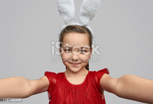 Cute girl in red dress and white ears posing and taking selfie on gray background
