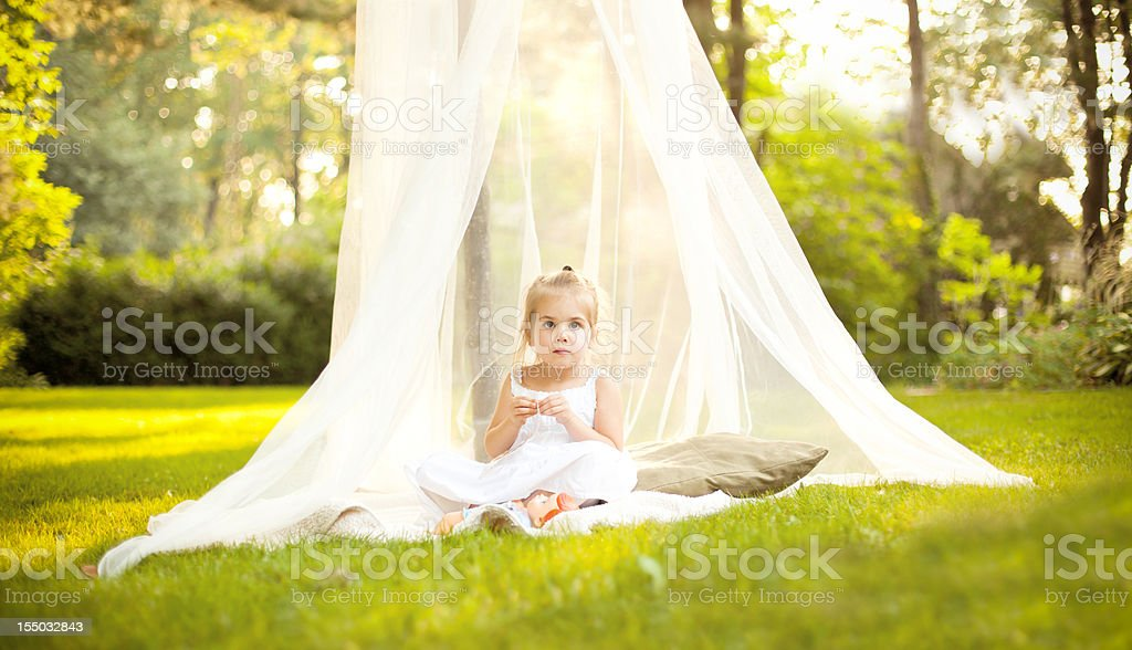 Little Girl in Canopy Under Tree stock photo