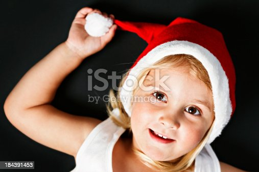 A little girl, lying on her back, tugging at her Christmas hat, photographed from above.