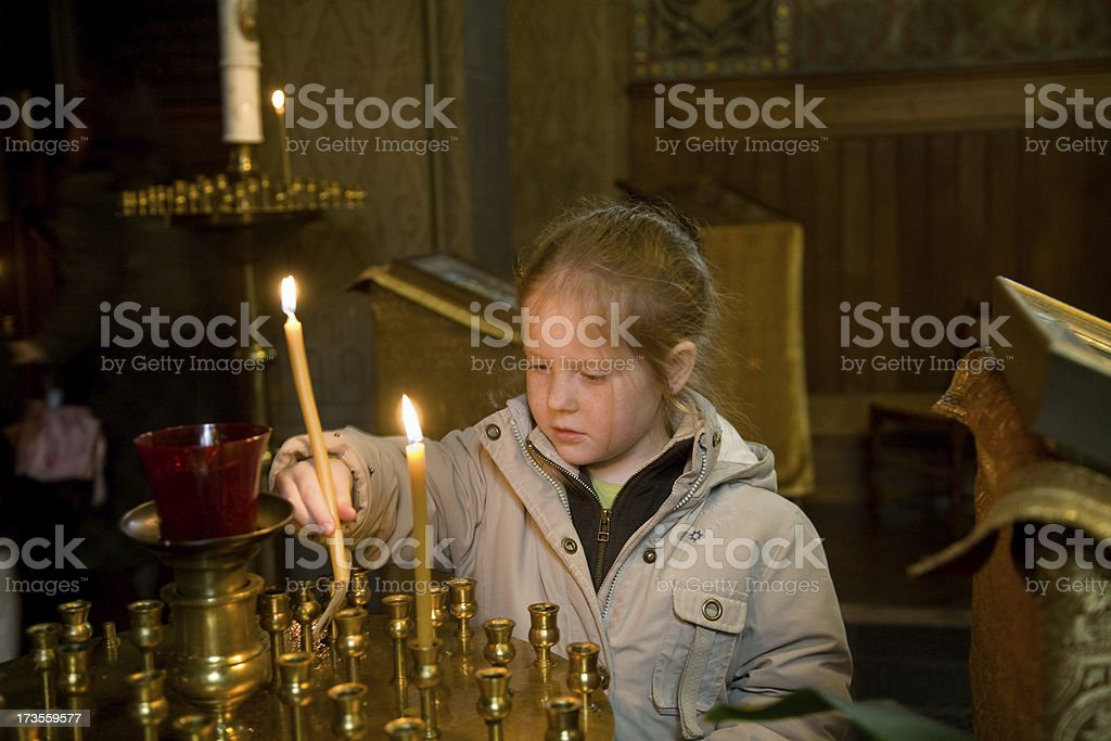 """Little girl in church, lighting candles """"Young girl in church, aged 6, lighting candles."""" 6-7 Years Stock Photo"""