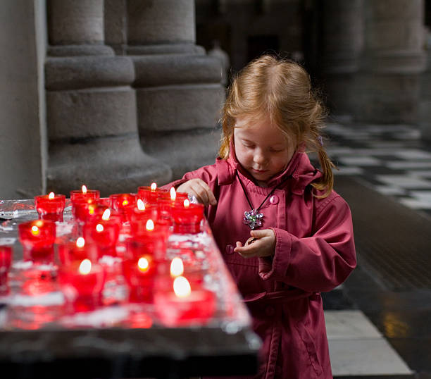 Little girl in church, paying for a candle stock photo