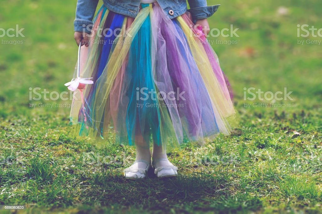 Little girl in colorful tutu skirt standing on green grass while holding magic wand stock photo