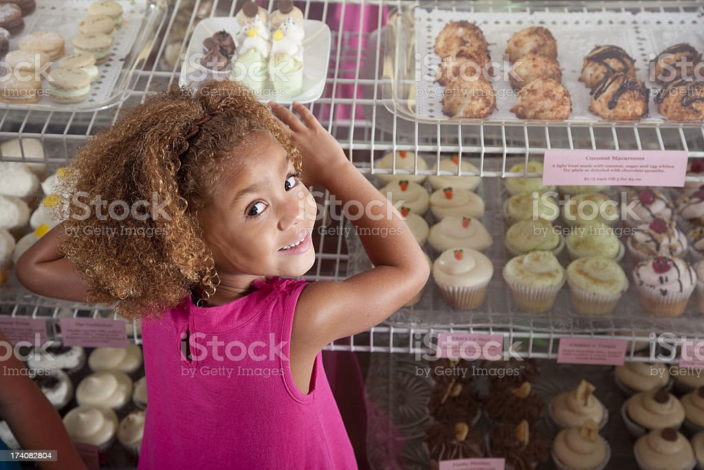 Little girl in cupcake store stock photo