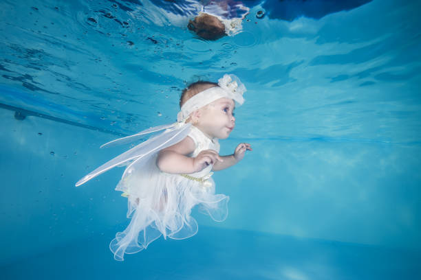 Little girl in fairy costume dives underwater in a swimming pool stock photo