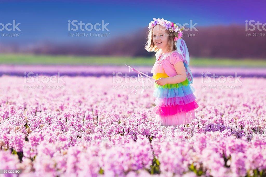 Kleines Mädchen in Märchen Kostüm spielen in Blumen Feld – Foto