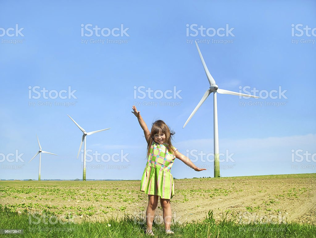 Little girl in front of windmills royalty-free stock photo