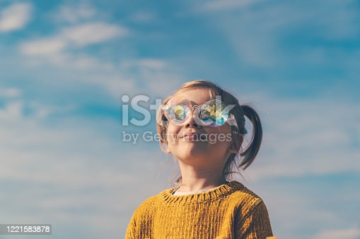 Five years little girl with ponytails, dressed in a yellow sweater and funny sunglasses is looking to the blue sky.