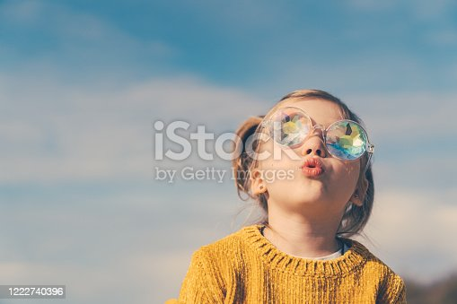 Five years little girl with ponytails, dressed in a yellow sweater and funny sunglasses is looking to the blue sky with a surprise.