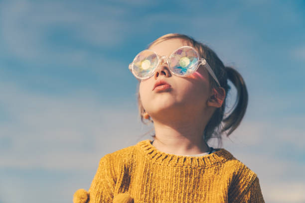 little girl in funny kaleidoscope glasses is looking to the sky with open mouth and curiosity. stock photo