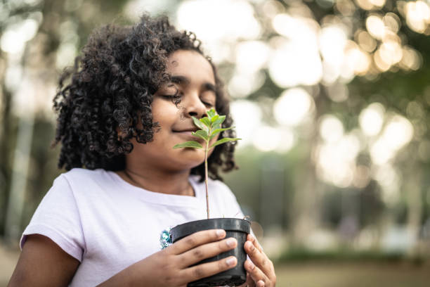 little girl in garden, smelling fresh plant - annusare foto e immagini stock