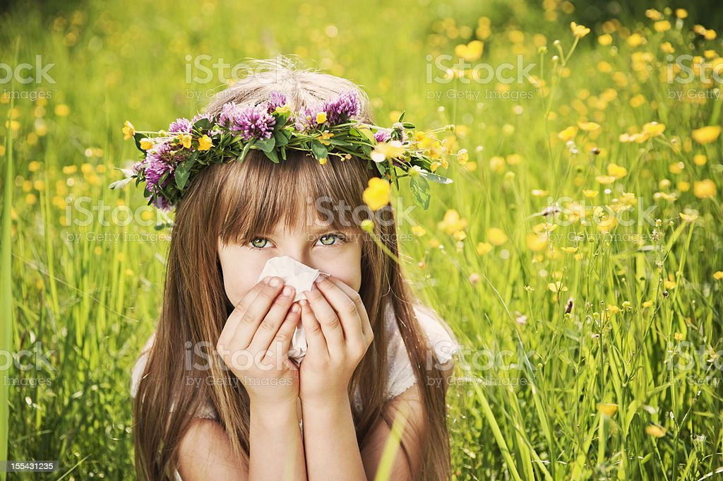 Little girl in grass cleaning her nose stock photo