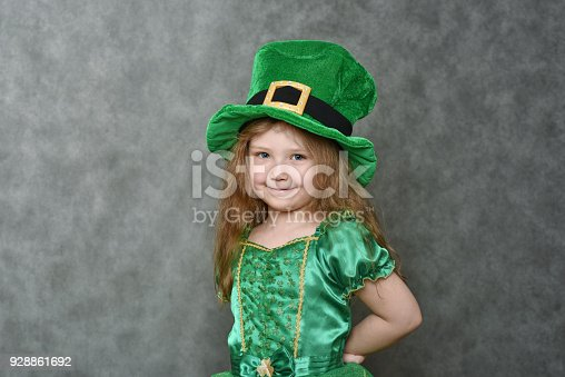 Little girl in green emerald dress and leprechaun top hat with golden buckle looking at camera