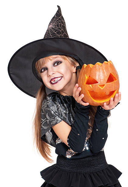 Little girl in halloween costume Portrait of little girl in black hat with pumpkin isolated on white background costume stock pictures, royalty-free photos & images