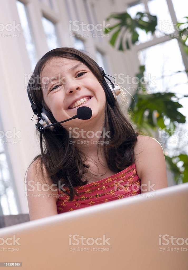 Little girl  in headphones with laptop royalty-free stock photo