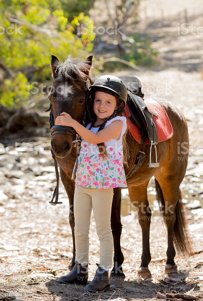 Little girl in helmet and riding gear posing with pony stock photo