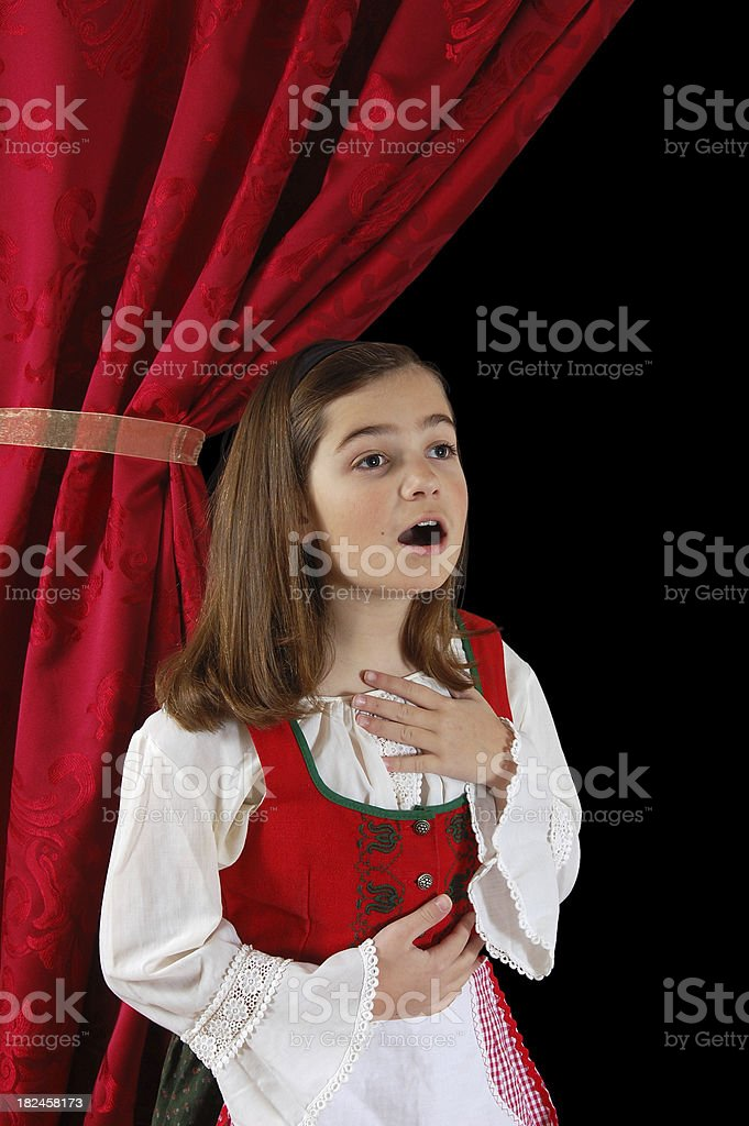 A little girl in her costume in Dirndl singing stock photo
