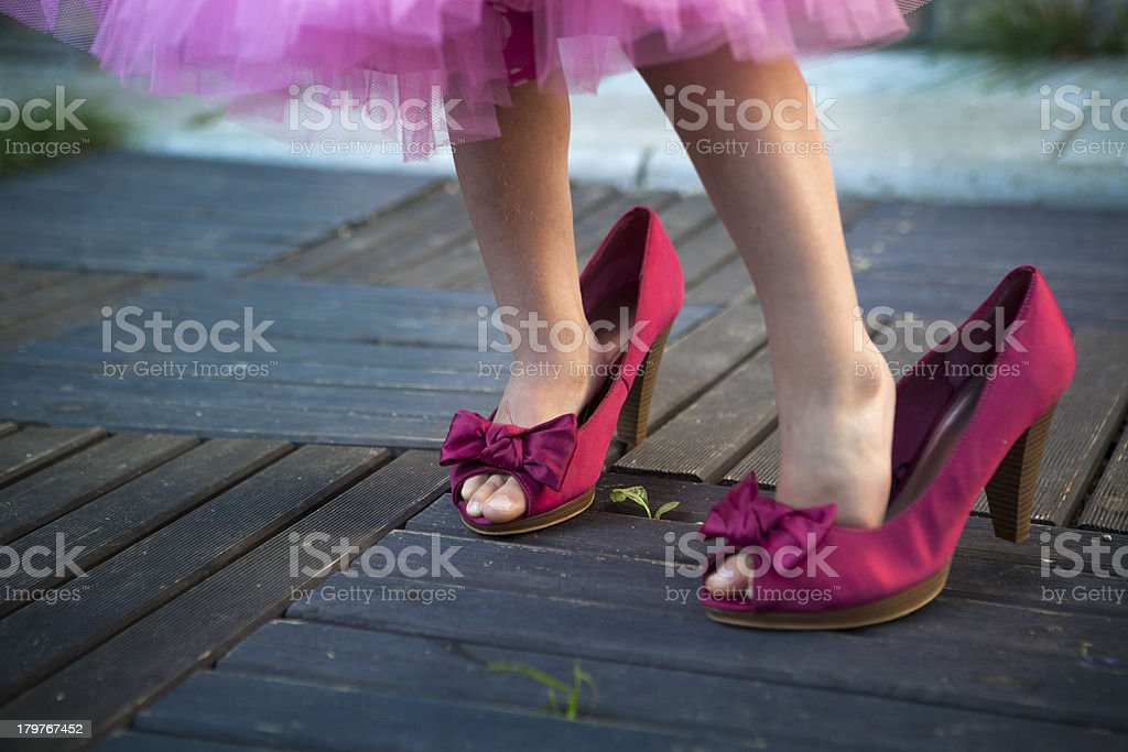 Little girl in her mother's high hells shoes stock photo