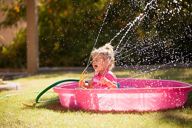 Little Girl in Kiddie Pool Little girl splashing in a pink kiddie pool with the hose and sprinkler spraying in her face. wading stock pictures, royalty-free photos & images
