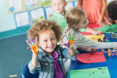 A cute little girl in art class in preschool or kindergarten.  She is sitting at a table with other children painting pictures.  She is looking at the camera, smiling, holding up her hands covered in paint.