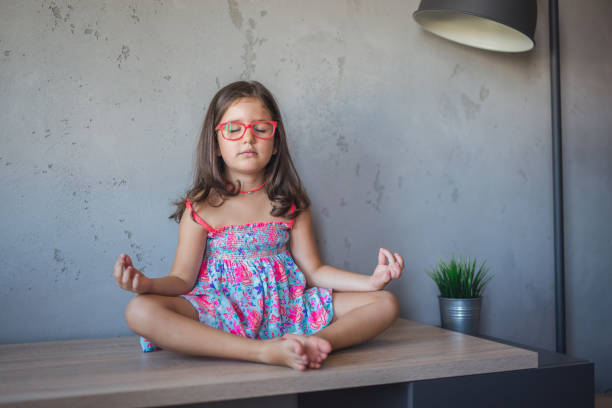 Little girl in lotus pose stock photo