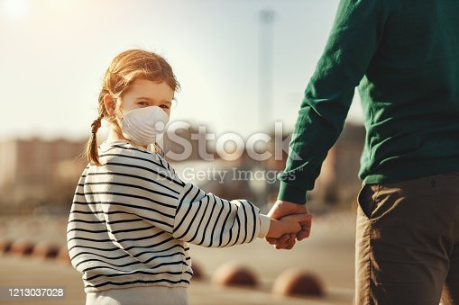 istock Little girl in medical mask holding hand of father 1213037028