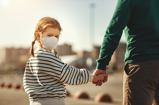 Back view of little girl in medical mask looking at camera over shoulder and holding hand of crop father while walking on parking lot during coronavirus outbreak