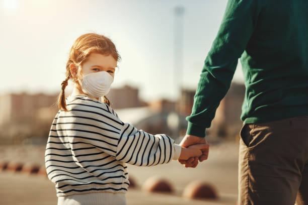 petite fille dans la main médicale de fixation de masque du père - masque enfant photos et images de collection